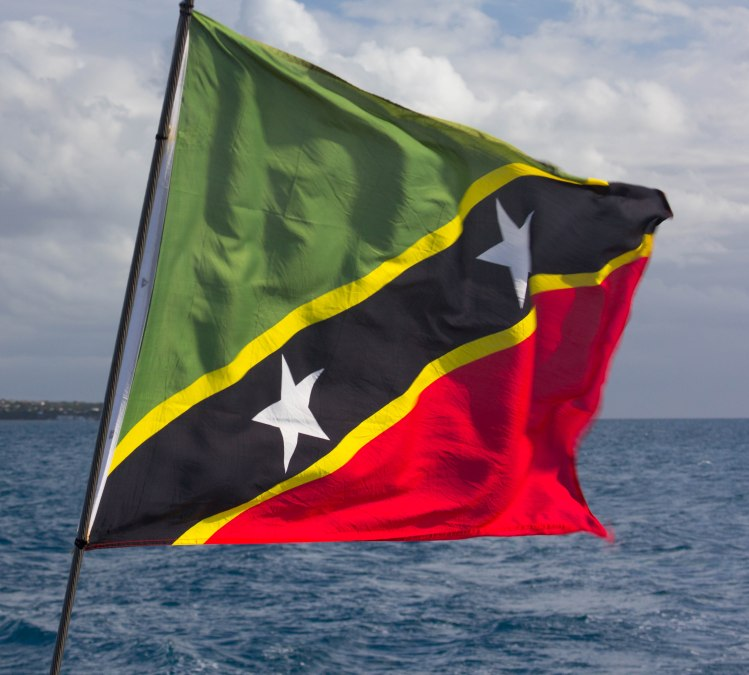 The National flag of St. Kitts & Nevis features green for fertile lands, yellow for year-round sunshine, black for the African heritage, and red for the struggle from slavery through colonialism to independence. It also displays two white stars on a black diagonal bar, symbols of hope and liberty.
